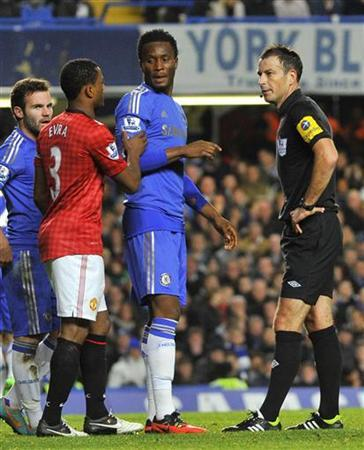 Referee Mark Clattenburg speaks with Chelsea's John Obi Mikel (C) and Manchester United's Patrice Evra after sending off Chelsea's Branislav Ivanovic during their English Premier League soccer match at Stamford Bridge in London October 28, 2012. REUTERS/Toby Melville