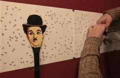 Artista russo Vasily Slonov trabalha em obra de arte retratando o ator Charles Chaplin, no Museu Krasnoyarsk, na Rússia. Um dos famosos conjuntos de chapéu-coco e bengala usados por Chaplin na era do cinema mudo será leiloado no domingo em Los Angeles, devendo alcançar um valor de 40 a 60 mil dólares, disse a casa de leilões Bonhams na terça-feira. 25/10/2012 REUTERS/Ilya Naymushin