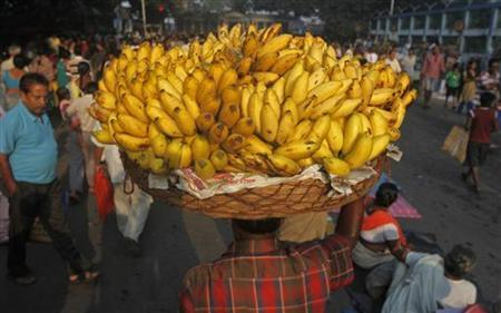 A vendor carries a basket of bananas to sell at a market in Kolkata October 15, 2012. REUTERS/Rupak De Chowdhuri