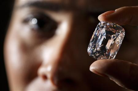An employee poses with the Archduke Joseph diamond during an auction preview at Christie's in Geneva in this file photo taken November 8, 2012. The 76 carat diamond is expected to fetch between 15 million and 20 million US dollars when it goes up for auction by Christie's in Geneva on November 13. REUTERS/Valentin Flauraud