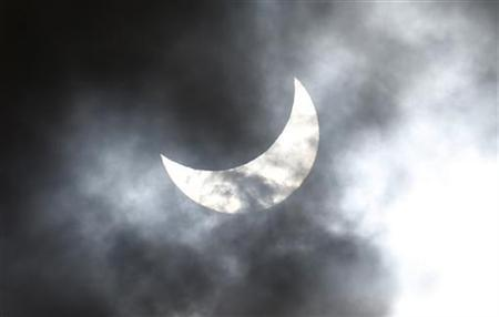 Clouds obscure the moon passing in front of the sun as it approaches a full solar eclipse in the northern Australian city of Cairns November 14, 2012. REUTERS/Tim Wimborne