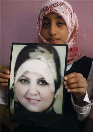 Zainab, the niece of Shaima Alawadi, holds the picture of her slain aunt at her father's house in Samawa, 270 km (160 miles) south of Baghdad, April 1, 2012. Shaima Alawadi, an Iraqi-American woman who was beaten to death in her U.S. home in a possible case of hate crime, was buried in her native Iraq on Saturday. REUTERS/Atef Hassan
