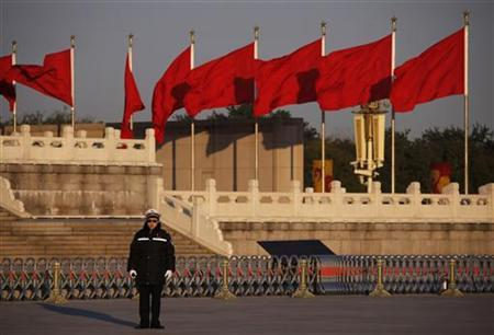 A police officer stands guard near the Great Hall of the People, the venue of the 18th National Congress of the Communist Party of China, before the closing ceremony, in Beijing, November 14, 2012. REUTERS/Petar Kujundzic