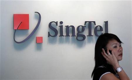 A woman speaks on a mobile phone in front of a SingTel logo at the company's headquarters in Singapore May 13, 2010. REUTERS/Vivek Prakash/Files