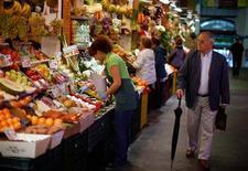 Un grupo de emprendedores españoles ha combinado los servicios de tienda de productos orgánicos, reparto a domicilio y recetario, en un intento de abrir un nuevo nicho de mercado en el comercio electrónico. En la imagen, una frutera elige setas en un mercado de Triana, en Sevilla, el 7 de noviembre de 2012. REUTERS/Marcelo del Pozo