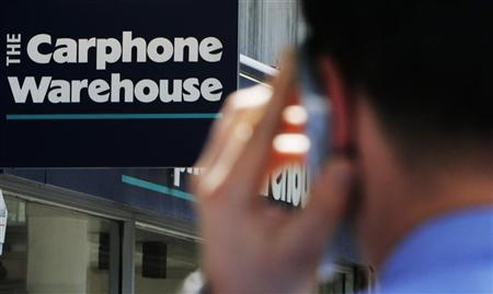 A man speaks on a mobile phone in front of a Carphone Warehouse shop in central London June 8, 2008. REUTERS/Luke MacGregor