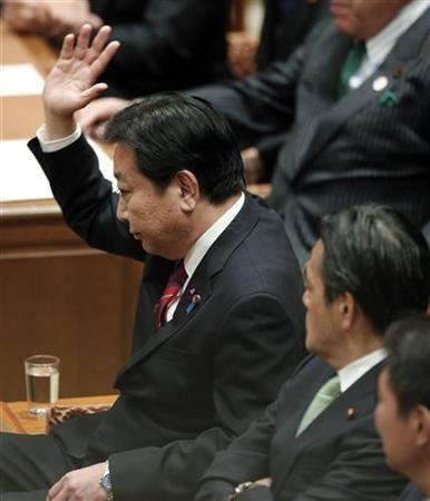 Japanese Prime Minister Yoshihiko Noda raises his hand at a parliamentary debate with main opposition Liberal Democratic Party (LDP) leader Shinzo Abe in Tokyo November 14, 2012. Noda told parliament on Wednesday he would be willing to dissolve parliament on November 16 and hold elections in December if the opposition agreed to pass electoral system reforms. REUTERS/Kim Kyung-Hoon (JAPAN - Tags: POLITICS ELECTIONS)