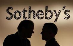 Мужчины разговаривают у стены с логотипом Sotheby's в галерее в Гонконге, 18 мая 2012 года. Sotheby's провел крупнейший за свою 268-летнюю историю аукцион, на котором полотно Марка Ротко ушло за $75 миллионов, а картина Джексона Поллока была продана за $40 миллионов - рекордную сумму для работ американского абстракциониста. REUTERS/Bobby Yip