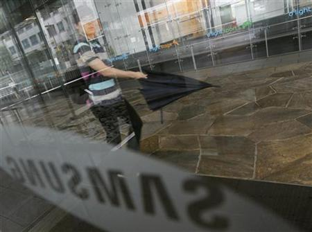 A man walks with an umbrella at the compound of the headquarters of Samsung Electronics in Seoul July 6, 2012. REUTERS/Lee Jae-Won