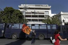 A protester walks past police buses in front of the Ministry of Administrative Reform during an anti-austerity rally by Greece's public servants unions in Athens November 13, 2012. REUTERS/Yorgos Karahalis (GREECE - Tags: POLITICS BUSINESS CIVIL UNREST)