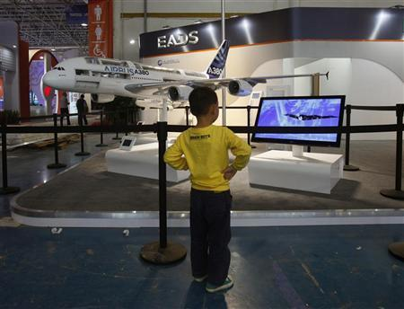 A child watches a video footage in front of a model of Airbus A380 passenger flight displayed at the China International Aviation & Aerospace Exhibition in the southern Chinese city of Zhuhai November 12, 2012. REUTERS/Bobby Yip