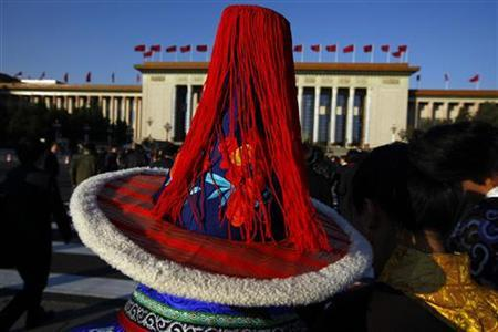 An ethnic minority delegate wearing a traditional costume walks towards the Great Hall of the People, before the closing session of the 18th National Congress of the Communist Party of China, in Beijing, November 14, 2012. REUTERS/David Gray (CHINA - Tags: POLITICS)
