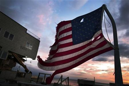A tattered flag flies at sunset on a pole in front of a home damaged by hurricane Sandy in the Brooklyn borough neighborhood of Seagate in New York November 13, 2012. REUTERS/Lucas Jackson