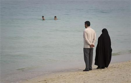 EDITORS' NOTE: Reuters and other foreign media are subject to Iranian restrictions on leaving the office to report, film or take pictures in Tehran. A couple watches swimmers as they stand on the beach of Kish Island, 1,250 kilometers (777 miles) south of Tehran April 26, 2011 . REUTERS/Caren Firouz/Files