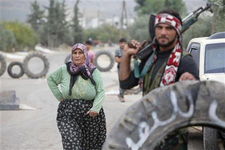 A woman walks near a member of the Free Syrian Army standing guard at a checkpoint they took over early on Monday after clashes with pro-government forces in Salqin city in Idlib October 22, 2012. REUTERS/Asmaa Waguih/Files