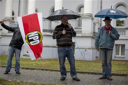 Supporters of the right-wing NPD party hold a rally against a march of refugees near Glienicke Bridge in Potsdam, October 5, 2012. REUTERS/Thomas Peter (GERMANY - Tags: POLITICS CIVIL UNREST SOCIETY IMMIGRATION)