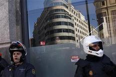 Policía y manifestantes se enfrentaron el miércoles en España e Italia mientras millones de trabajadores iban a la huelga en Europa para protestar contra los recortes que consideran han empeorado la crisis económica. Cientos de vuelos se cancelaron, las fábricas de automóviles y puertos se quedaron parados y los trenes apenas circulaban en España y Portugal, donde los sindicatos celebran su primera huelga general coordinada. En la imagen, una empleada de un restaurante de comida rápida mira la presencia policial durante la huelga general en Madrid el 14 de noviembre de 2012. REUTERS/Susana Vera