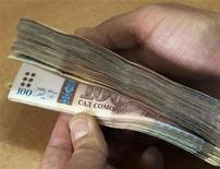 Сотрудник Агроинвестбанка пересчитывает таджикские сомони в офисе в Душанбе 2 февраля 2012 года. Парламент Таджикистана в среду одобрил $2,54-миллиардный план расходов казны на следующий год, нацеленный на сокращение зависимости беднейшей страны Средней Азии от импортных продовольствия и топлива. REUTERS/Nozim Kalandarov