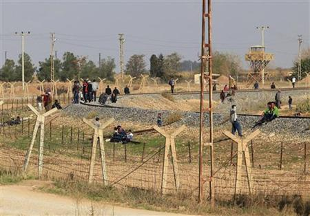 Residents gather around a rail road in the Syrian town of Ras al-Ain, as seen from the Turkish border town of Ceylanpinar, Sanliurfa province November 14, 2012. A Syrian warplane bombed the town of Ras al-Ain near the Turkish border for a third day on Wednesday as forces loyal to President Bashar al-Assad pressed an air assault to dislodge rebels. REUTERS/Stringer (TURKEY - Tags: POLITICS CONFLICT CIVIL UNREST)