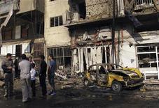 Moradores juntam-se perto de local onde ocorreu explosão de carro-bomba em bairro de Bagdá. 14/11/2012 REUTERS/Mohammed Ameen