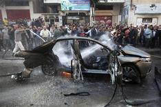Люди тушат автомобиль после авиаудара израильских ВВС в Газе 14 ноября 2012 года. Израиль уничтожил командующего боевым крылом палестинского исламистского движения ХАМАС Ахмеда Аль-Джаабари, нанеся по Сектору Газа массированный авиаудар и поставив нестабильный регион перед угрозой новой войны, сообщили ХАМАС и израильские спецслужбы. REUTERS/Ali Hassan