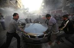 Palestinians try to remove the remains of a car after an Israeli air strike in Gaza City November 14, 2012. REUTERS/Ali Hassan (GAZA - Tags: POLITICS CIVIL UNREST)