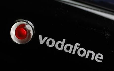 A Vodafone logo is seen on a mobile internet dongle connected to a laptop in London November 9, 2010. REUTERS/Suzanne Plunkett