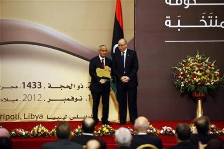 Outgoing prime minister Abdurrahim El-Keib (R) presents a map of Libya to newly appointed Libyan Prime Minister Ali Zeidan at the handover ceremony in Tripoli November 14, 2012. REUTERS/Ismail Zitouny