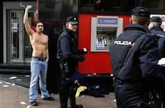 Un total de 110 personas han sido detenidas en toda España durante la jornada de huelga que vive el país el miércoles en protesta por los duros recortes del Gobierno contra la crisis, informó la Policía Nacional. En la imagen, un hombre gesticula mientras es identificado por la policía en Oviedo el 14 de noviembre de 2012. REUTERS/Eloy Alonso