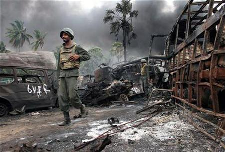 In this photograph released by the Sri Lankan military on May 18, 2009 shows what the army says are government troops walking near burnt or burning vehicles in the area inside the war zone near the town of Mullaittivu. REUTERS/Sri Lankan Government/Handout