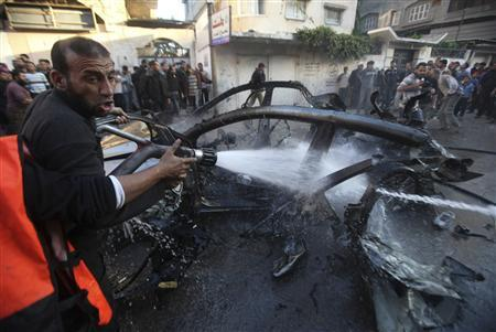 Palestinians extinguish a fire after an Israeli air strike on a car in Gaza City November 14, 2012. REUTERS/Ali Hassan