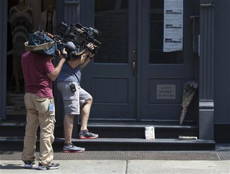 TV camera crew film flowers that were placed outside the family home of Etan Patz, who disappeared 33 years ago in New York May 26, 2012. REUTERS/Andrew Kelly