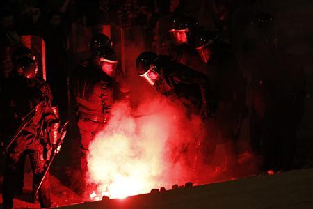 Policemen watches a flare during clashes with protesters at the 24-hour nationwide general strike near the Parliament in Lisbon, November 14, 2012. Spanish and Portuguese workers will stage the first coordinated general strike across the Iberian Peninsula on Wednesday, shutting transport, grounding flights and closing schools to protest against spending cuts and tax hikes. REUTERS/Hugo Correia