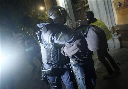 A policeman detains a protester during a 24-hour nationwide general strike in central Madrid November 14, 2012. REUTERS/Susana Vera