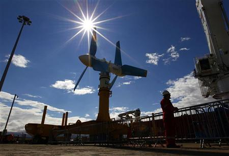 An engineer stands near the Atlantis Resources AK-1000 tidal energy turbine before it is shipped to the European Marine Energy Centre test site in the Orkney Islands from the port at Invergordon, northern Scotland August 12, 2010. REUTERS/David Moir