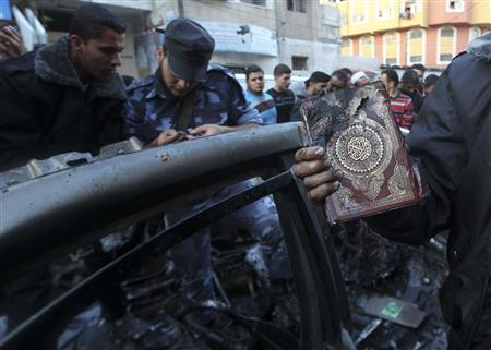 A man holds a copy of Koran after an Israeli air strike on a car of Hamas's military chief in Gaza City November 14, 2012. Hamas's military chief was killed when his car was hit by an Israeli airstrike on Wednesday, the Palestinian Islamist group said, with multiple Israeli attacks rocking the Gaza Strip. Hamas said Ahmed Al-Jaabari, who ran the organisation's armed wing, the Izz el-Deen Al-Qassam, died along with a passenger after their car was targeted by an Israeli missile. REUTERS/Mohammed Salem