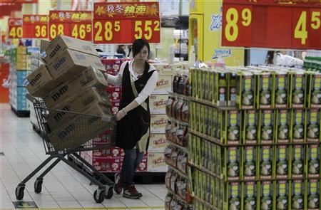 An employee pulls a trolley loaded with boxes of products at a supermarket in Wuhan, Hubei province October 13, 2011. REUTERS/Stringer