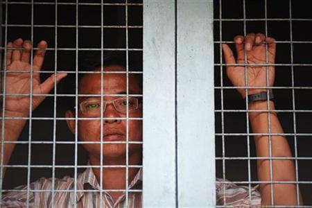 Myo Min, a 36-year-old electrical repairman, poses for a photo at the doors of a house in Yangon May 25, 2012. REUTERS/Damir Sagolj