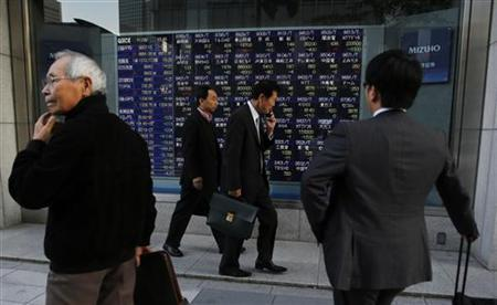 Pedestrians are seen in front of an electronic board displaying share prices outside a brokerage in Tokyo November 8, 2012. REUTERS/Yuriko Nakao