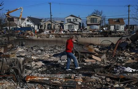 A woman walks through her burnt house in the Breezy Point neighborhood which were left devastated by Hurricane Sandy in the New York borough of Queens on November 14, 2012. REUTERS/Adrees Latif