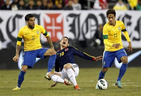 Brazil's Daniel Alves (L) tackles Colombia's James Rodriguez (C) as Brazil's Neymar looks on (R) during their international friendly soccer match in East Rutherford, New Jersey, November 14, 2012. REUTERS/Adam Hunger