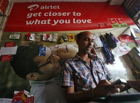 A shopkeeper uses a mobile phone inside a Bharti Airtel store in Agartala, November 7, 2012. REUTERS/Jayanta Dey/Files