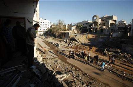A Palestinian man looks at the damage after Israeli air strikes in Gaza City November 15, 2012. REUTERS/Suhaib Salem (GAZA - Tags: POLITICS CIVIL UNREST CONFLICT)