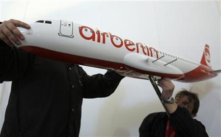 Exhibition workers put final hands on an aircraft model by Air Berlin in preparations for the upcoming ITB tourism fair in Berlin (Archiv). REUTERS/Tobias Schwarz (GERMANY)