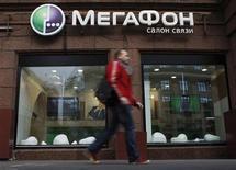 Мужчина проходит мимо салона связи Мегафон в Москве, 4 сентяюря 2012 года. Второй по величине мобильный оператор РФ Мегафон определил диапазон цены акции и GDR в ходе IPO в $20-25, что позволяет компании привлечь минимум $1,691 миллиарда до исполнения опциона на переподписку, объявил Мегафон в четверг. REUTERS/Maxim Shemetov