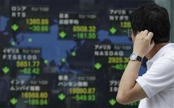Мужчина проходит мимо информационного табло с биржевыми индексами в Токио, 23 июля 2012 года. Иена упала до минимума 6,5 месяцев к доллару после того, как лидер главной оппозиционной партии Японии призвал Банк Японии к решительному смягчению политики для поддержки экономического роста. REUTERS/Yuriko Nakao