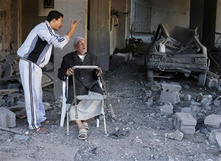 A Palestinian man sits inside his damaged house after Israeli air strikes in Gaza City November 15, 2012. REUTERS/Suhaib Salem
