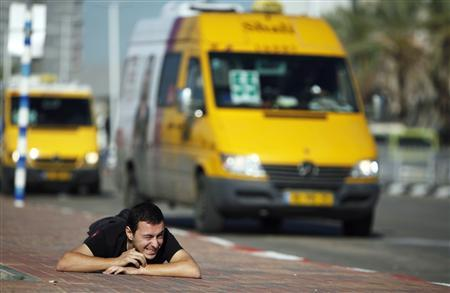 An Israeli man takes cover as a siren sounds warning of incoming rockets in Ashdod November 15, 2012. REUTERS/Amir Cohen