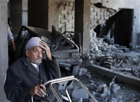 A Palestinian man sits inside a damaged house after Israeli air strikes in Gaza City November 15, 2012. REUTERS/Suhaib Salem