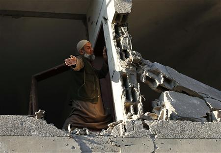 A Palestinian man checks his damaged house after Israeli air strikes in Gaza City November 15, 2012. REUTERS/Suhaib Salem